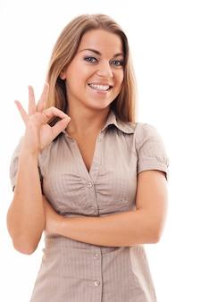 Młoda kobieta robi ok gest ręką. dobra robota!