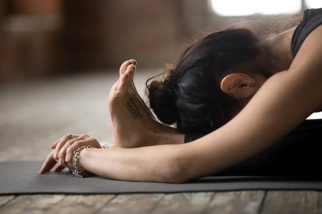 Młoda kobieta robi paschimottanasana ćwiczeniu