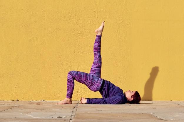 Młoda kobieta robi pilates na zewnątrz - koncepcja fitness