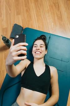 Młoda kobieta robi połączenie wideo i uśmiecha się podczas odpoczynku po zajęciach jogi w domu