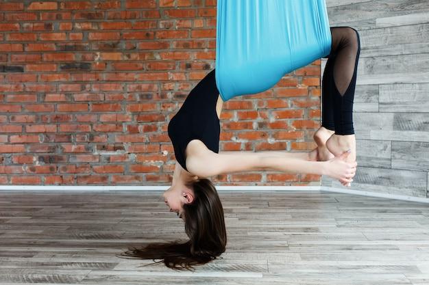 Młoda kobieta robi powietrzny joga na błękitnym wiszącym hamaku w gym
