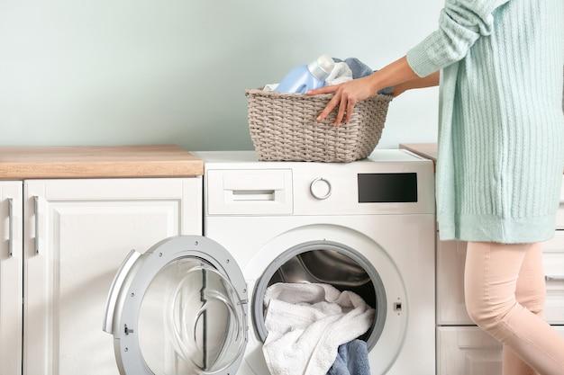 Młoda kobieta robi pranie w domu