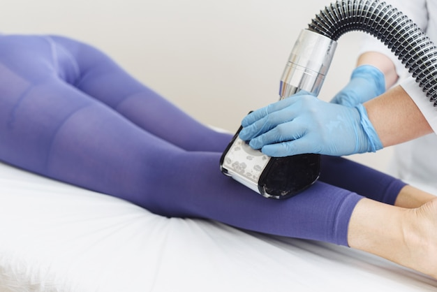 Młoda kobieta robi procedurę nogi lpg. reklama.