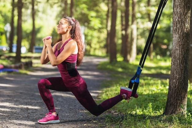 Młoda kobieta robi przysiady na jednej nodze z pasami fitness przymocowanymi do drzewa w parku