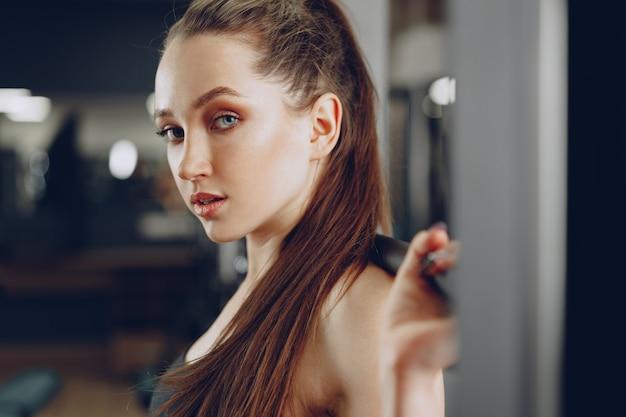 Młoda kobieta robi przysiady ze sztangą w aparacie siłowni