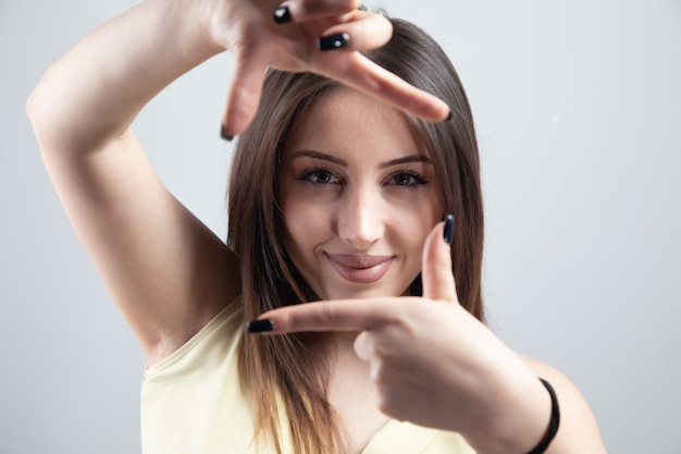Młoda kobieta robi ramce rękami.