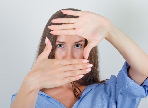 Młoda kobieta robi ramę palców w niebieskiej koszuli i wygląda pewnie