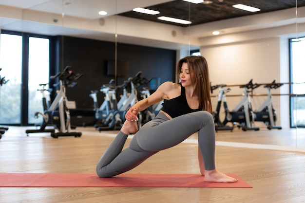 Młoda kobieta robi rozciągających ćwiczeń w siłowni