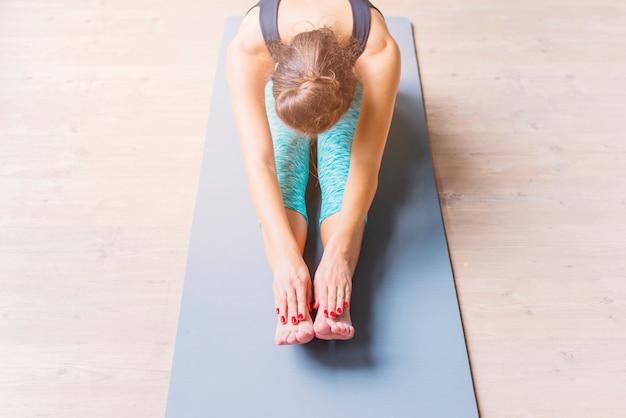 Młoda kobieta robi rozciągania ćwiczeniu na joga macie