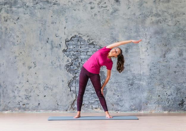 Młoda kobieta robi rozciągania ćwiczeniu w joga klasie