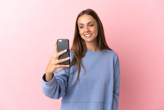Młoda kobieta robi selfie na odosobnionym różowym tle