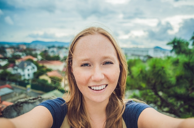 Młoda kobieta robi selfie na tle miasta dalat