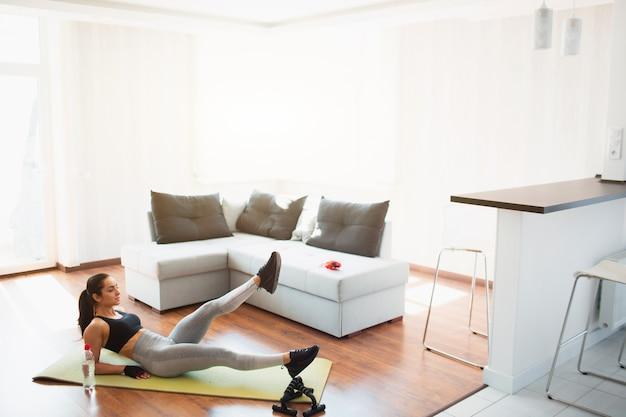 Młoda kobieta robi sporta treningowi w pokoju podczas kwarantanny. dobrze wyprofilowana dziewczyna o cudownym ciele robi nożyczkowe nogi ćwicząc na macie. opierając się na rękach. rozciąganie nóg w górę iw dół.