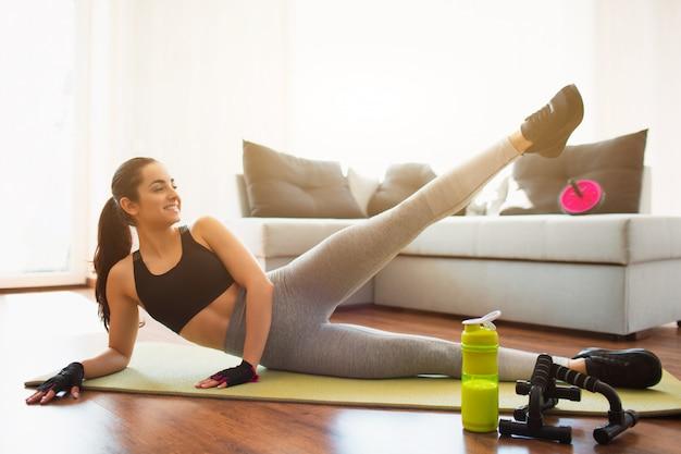 Młoda kobieta robi sporta treningowi w pokoju podczas kwarantanny. dziewczyna leży na biodrze i przytrzymaj lewą nogę do góry. rozciąganie dolnej części ciała. ćwiczyć samotnie w pokoju.
