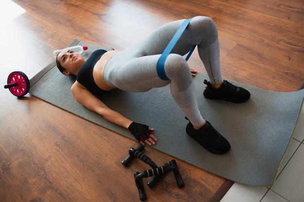 Młoda kobieta robi sporta treningowi w pokoju podczas kwarantanny. leżąc na macie i trzymaj ciało w pozycji mostka pośladkowego. elastyczna taśma wzmacniająca na nogawkach.