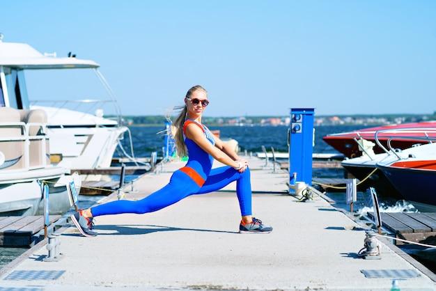 Młoda kobieta robi sportom przy dokiem