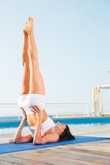 Młoda kobieta robi stanąć na ramię na macie do jogi na zewnątrz