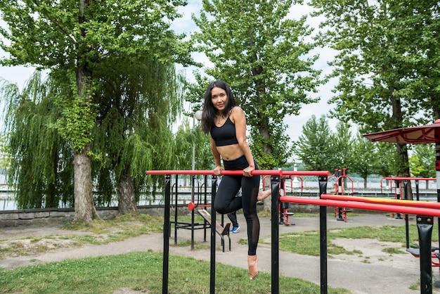 Młoda kobieta robi street workout na poziomym pasku, w letni poranek. pojęcie zdrowego stylu życia