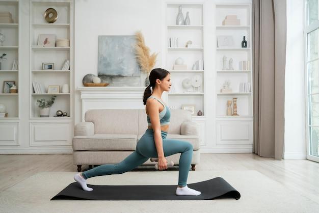Młoda kobieta robi swój trening w domu na macie fitness