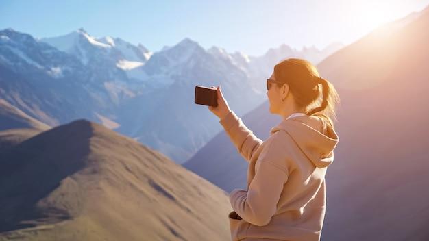 Młoda kobieta robi telefonem zdjęcia pięknego górskiego krajobrazu z ośnieżonymi szczytami górskimi.