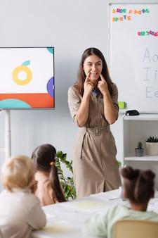 Młoda kobieta robi terapię mowy z dziećmi w swojej klinice