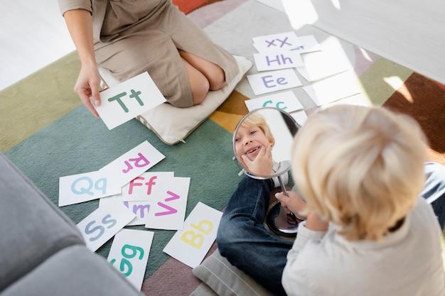Młoda kobieta robi terapię mowy z małym blond chłopcem