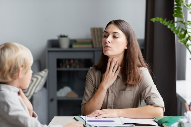 Młoda kobieta robi terapię mowy z małym chłopcem