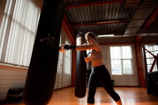 Młoda kobieta robi trening bokserski na siłowni, ma na sobie rękawice bokserskie i uderza w worek treningowy.