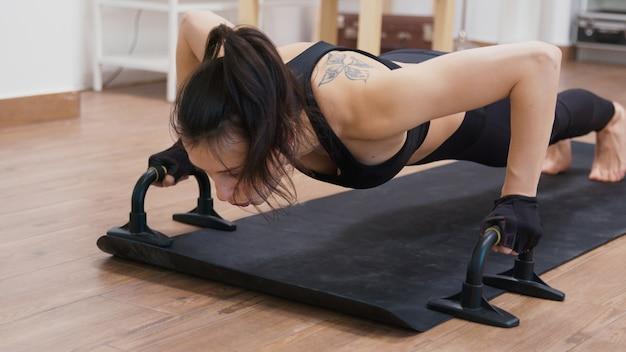 Młoda kobieta robi trening siłowy w domu za pomocą barów push-up.