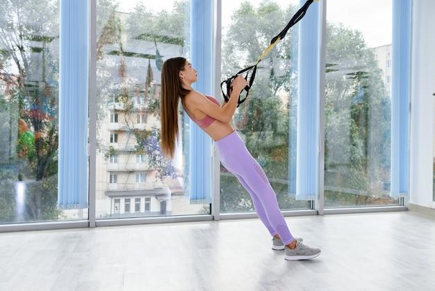 Młoda kobieta robi trening z trx pasy treningu ramion w siłowni fitness. sport dla zdrowego stylu życia.