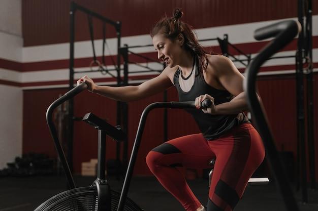 Młoda kobieta robi treningu cardio przy użyciu roweru stacjonarnego na siłowni.