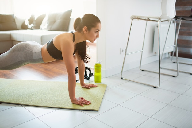 Młoda kobieta robi treningu sportowego w pokoju podczas kwarantanny. przekrój modelu fitness w pozycji pełnej długości deski. silny wygląd kobiety ma ćwiczenia w pokoju.