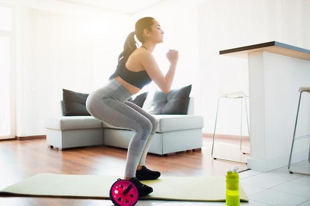 Młoda kobieta robi treningu sportowego w pokoju podczas kwarantanny. robi przysiady na macie do jogi w pokoju. skoncentrowany trening.