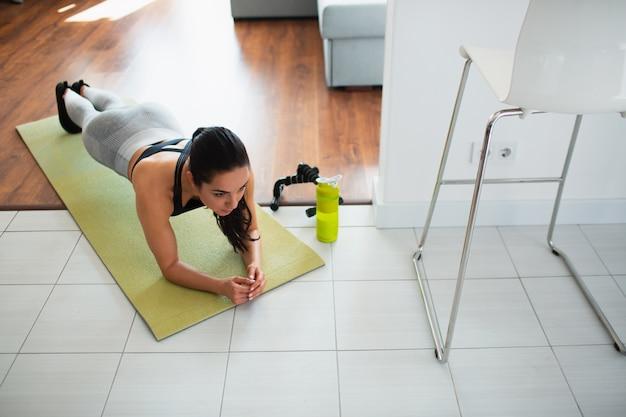 Młoda kobieta robi treningu sportowego w pokoju podczas kwarantanny. widok dziewczyny stoją w pozycji deski. silna kobieta ćwicząc samotnie w pokoju.