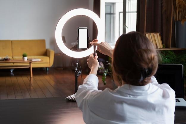 Młoda kobieta robi vloga do makijażu swoim smartfonem