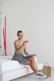 Młoda kobieta robi zakupy online, siedząc w domu na łóżku