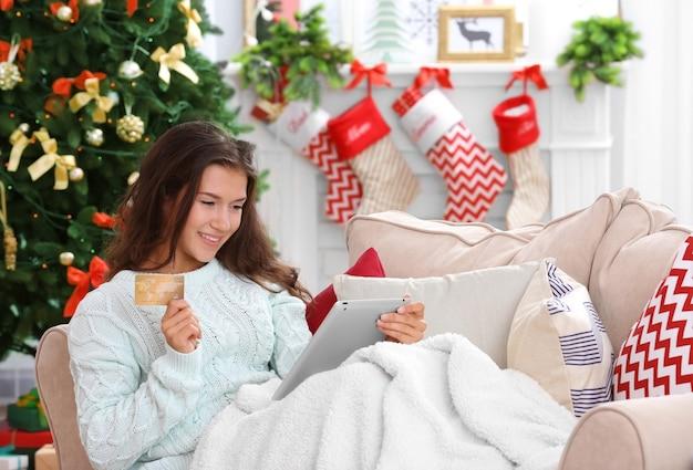 Młoda kobieta robi zakupy online z kartą kredytową w domu na boże narodzenie