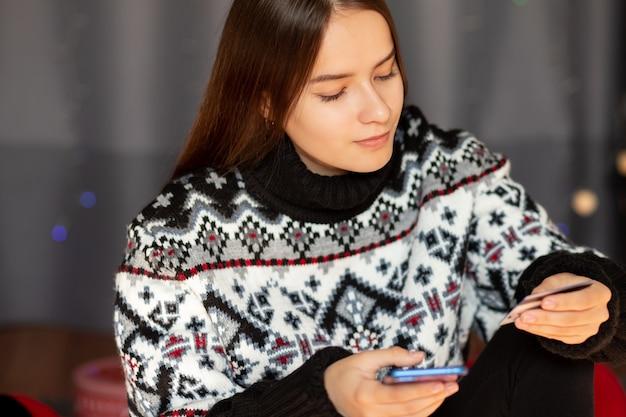 Młoda kobieta robi zakupy online z karty kredytowej podczas świątecznej wyprzedaży za pomocą telefonu komórkowego