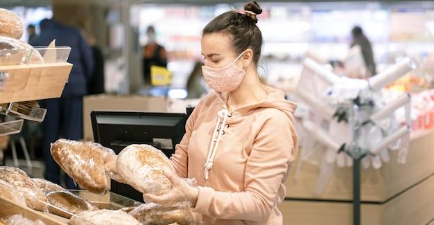 Młoda kobieta robi zakupy w supermarkecie podczas epidemii wirusa.