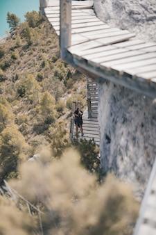 Młoda kobieta robi zdjęcia na wiszących drewnianych schodach