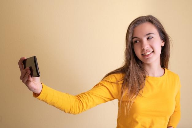Młoda kobieta robi zdjęcie swoim telefonem komórkowym na żółtym tle