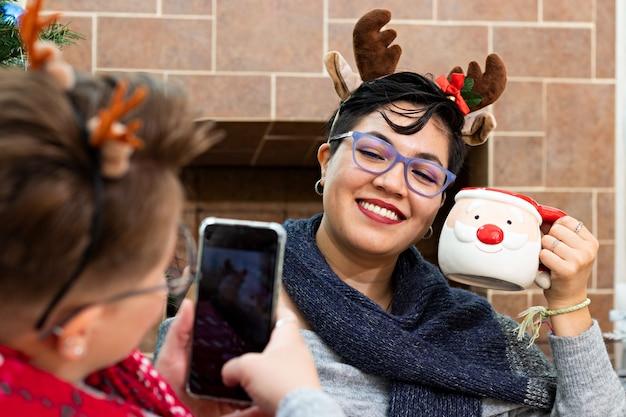 Młoda kobieta robi zdjęcie swojej dziewczynie z bożonarodzeniowym kubkiem przed choinką