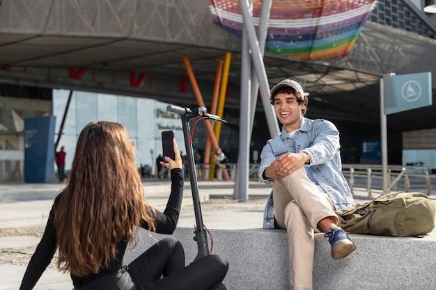 Młoda kobieta robi zdjęcie swojemu przyjacielowi obok skutera