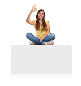 Młoda kobieta robi znak homologacji siedzi na banerze