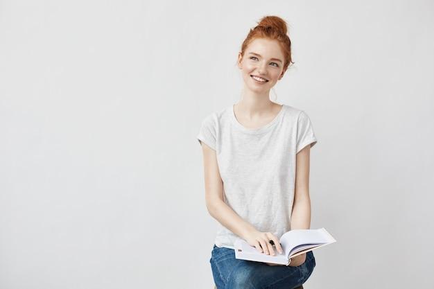 Młoda kobieta, robiąc notatki do pamiętnika, uśmiechając się wesoło.