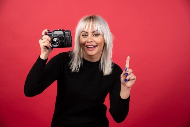 Młoda kobieta robienie zdjęć aparatem na czerwonym tle. wysokiej jakości zdjęcie
