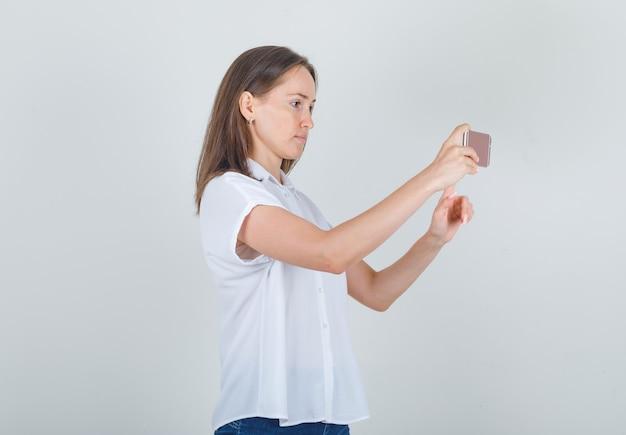 Młoda kobieta robienie zdjęć na smartfonie w białej koszuli, dżinsach i patrząc skoncentrowany.