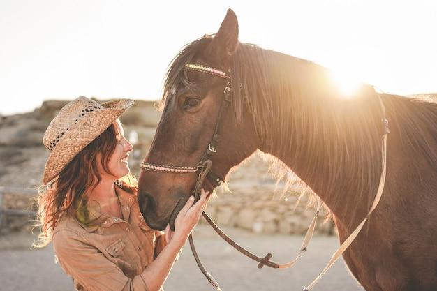 Młoda kobieta rolnik bawi się ze swoim bezgranicznym koniem w słoneczny dzień na ranczo zagroda