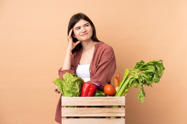 Młoda kobieta rolnik ze świeżo zebranych warzyw w polu, mając wątpliwości