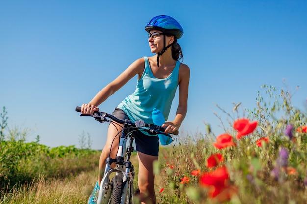 Młoda kobieta rowerzysta jedzie bicykl w lato maczka polu. sprawny dziewczyna cieszy się krajobraz.
